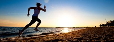 Dramatic action photo of athlete running along a beach at sunset. Stock photos videos Australia